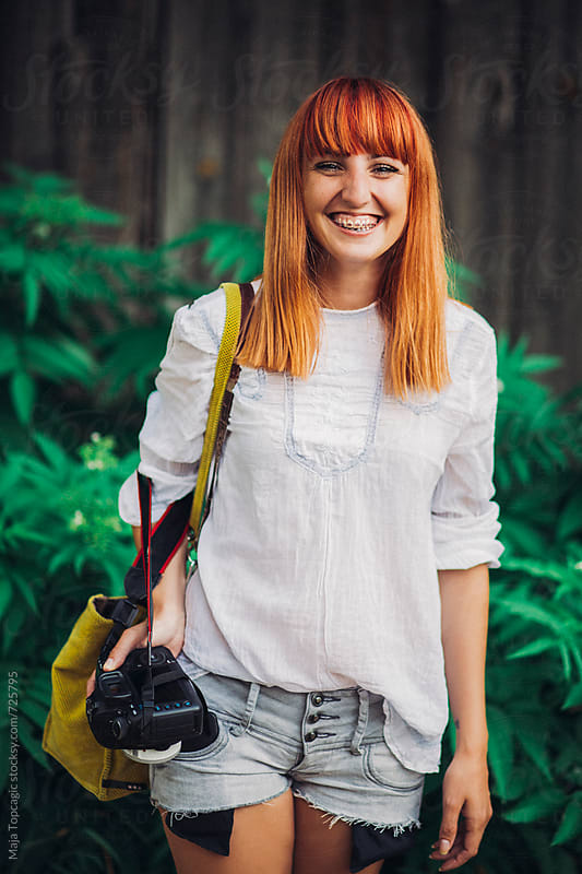 Female photographer smiling outdoors by Maja Topcagic for Stocksy United