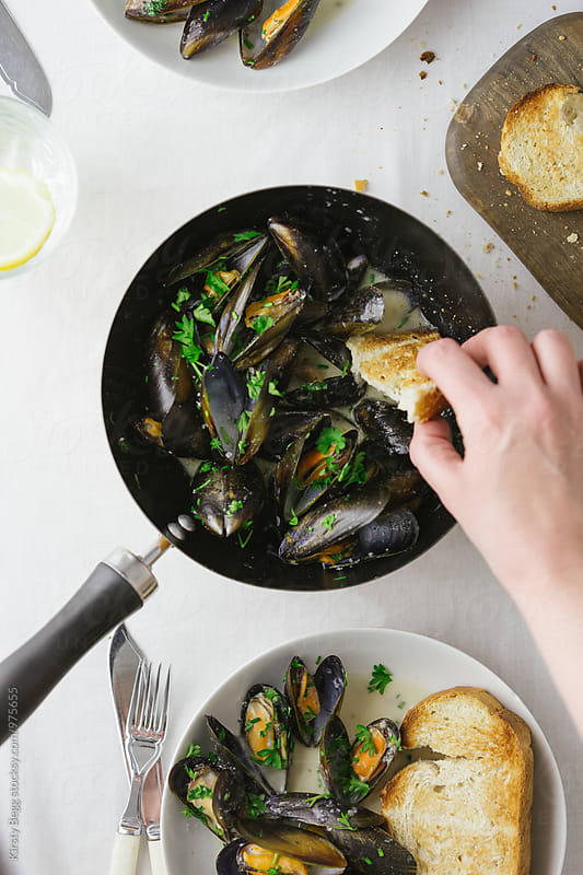 Woman dips toasted bread into garlic butter sauce and mussels by Kirsty Begg for Stocksy United