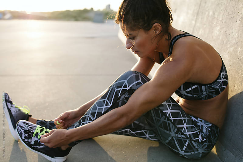 Woman tying shoes during exercise by Jacob Lund for Stocksy United