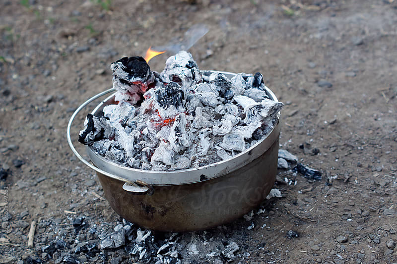 Burning coals cooking a dutch oven by Tana Teel for Stocksy United