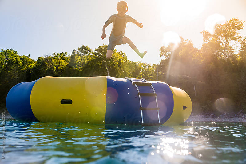 Boy Jumping Into Summer Lake From Water Trampoline At Cottage at Sunset by JP Danko for Stocksy United