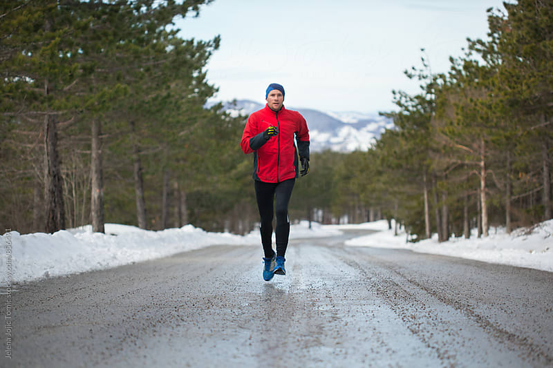 Running on a mountain road during the winter day by Jelena Jojic Tomic for Stocksy United