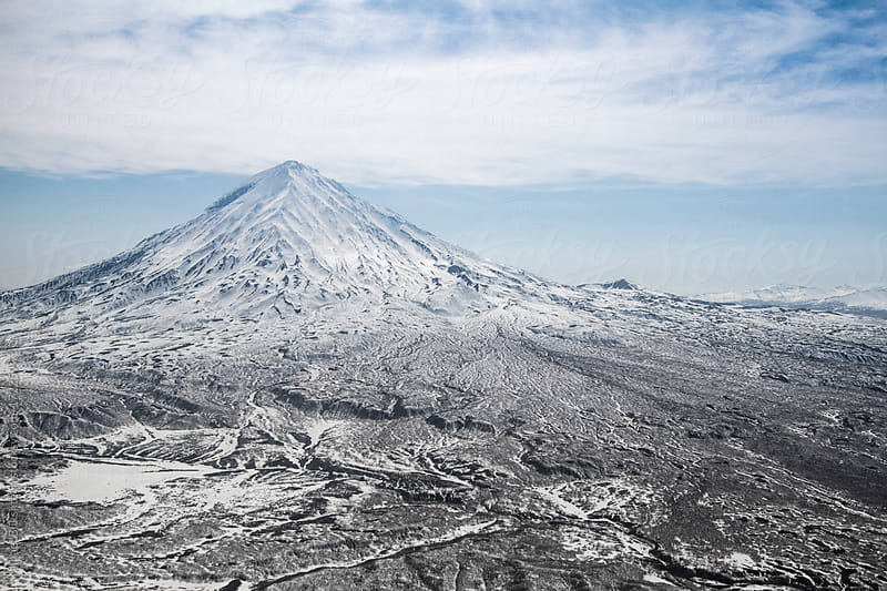 Aerial view of a snow-covered extinct volcano and plateau by Mihael Blikshteyn for Stocksy United