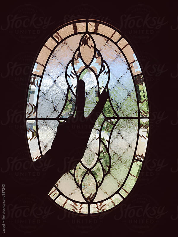 Silhouette of hand showing peace sign in front of oval window by Jacqui Miller for Stocksy United