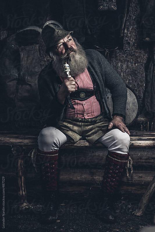 old full bearded man in lederhosen sitting inside a wooden cabin smoking a pipe by Leander Nardin for Stocksy United