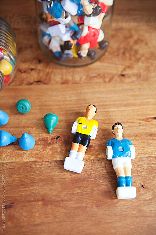 a collection of vintage toys arranged in jars on a desktop by Natalie JEFFCOTT for Stocksy United