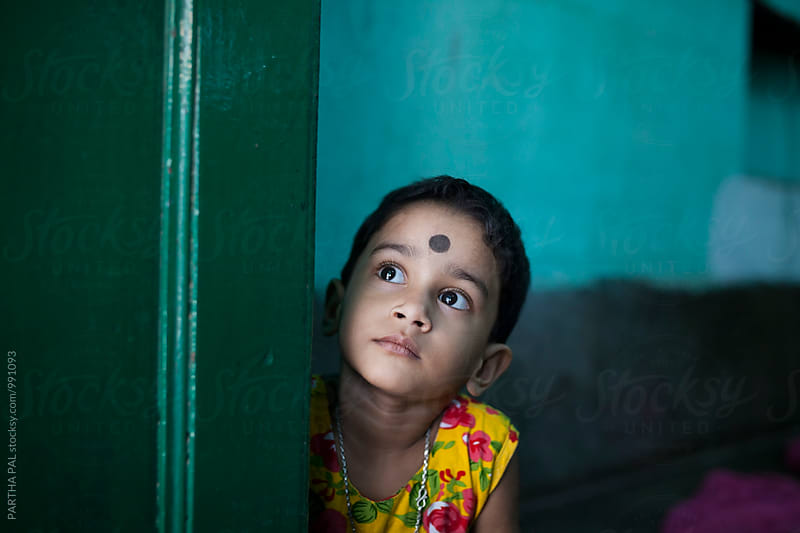 A little girl looking upwards behind a door by PARTHA PAL for Stocksy United