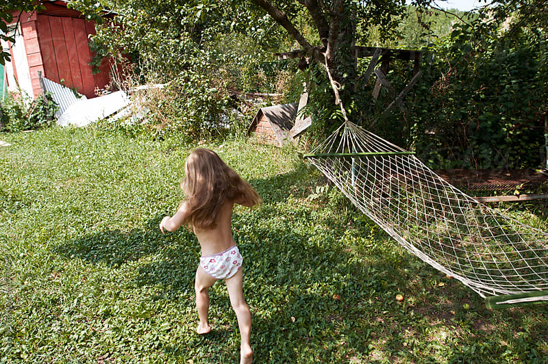 Little girl running on the grass by Svetlana Shchemeleva for Stocksy United