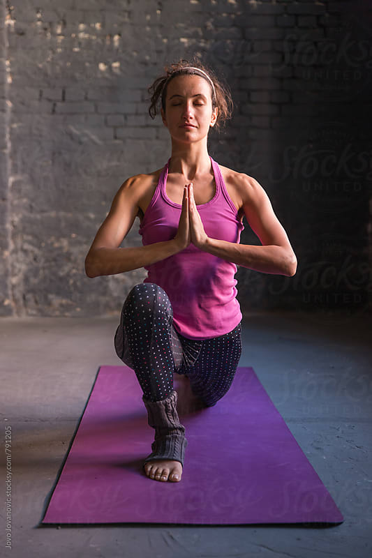 Woman practicing yoga in a modern looking studio by Jovo Jovanovic for Stocksy United