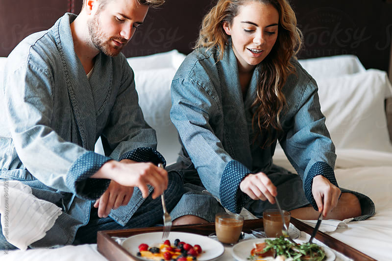 Young couple enjoying room service in bed by Kayla Snell for Stocksy United