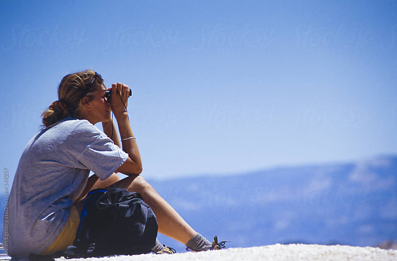 Girl sitting and looking at landscape with binoculars. by Soren Egeberg for Stocksy United