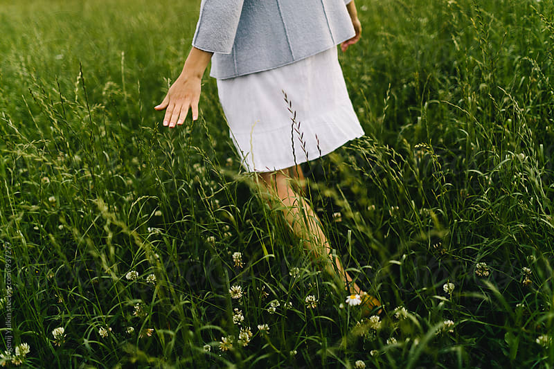 Female hand stroking the grass  by Evgenij Yulkin for Stocksy United
