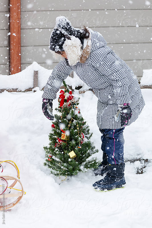 a girl playing snow with christmas tree by jira Saki for Stocksy United