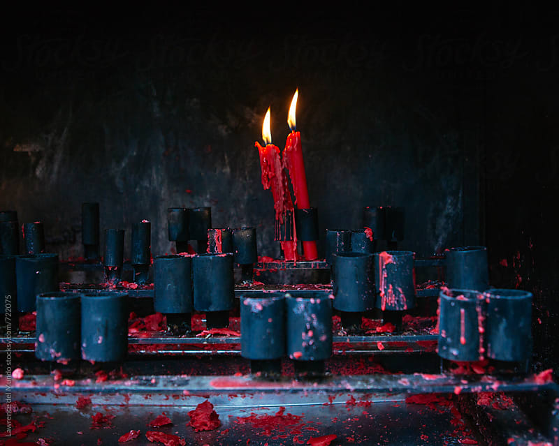 A couple of lighted red candles in a temple by Lawrence del Mundo for Stocksy United