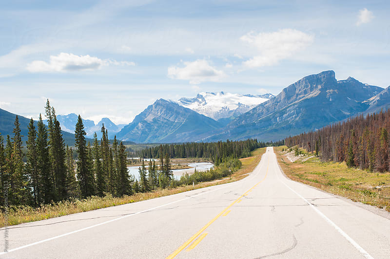 Highway with Rocky Mountains by Peter Wey for Stocksy United