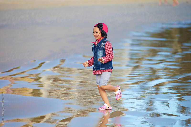 happy asian girl playing on the beach by Bo Bo for Stocksy United