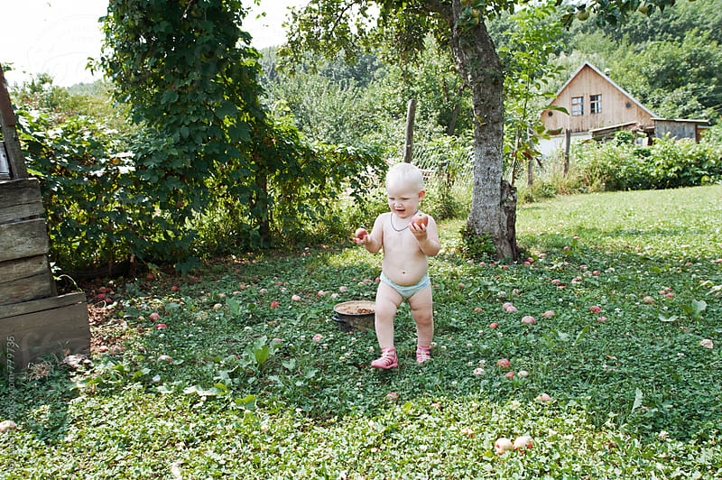 Little girl in the apple orchard by Svetlana Shchemeleva for Stocksy United
