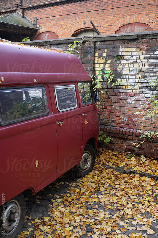 Old camper van in front of a wall in fall by Marcel for Stocksy United