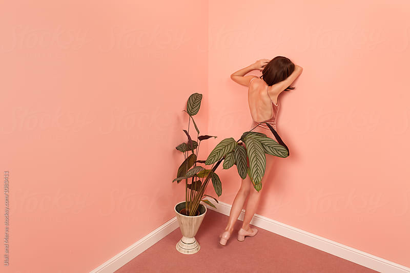 fashionable woman leaning against a pink wall by Ulaş and Merve for Stocksy United