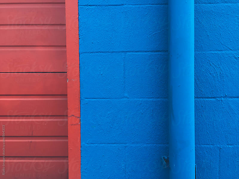 Painted red and blue building with gutter pipe, close up by Paul Edmondson for Stocksy United