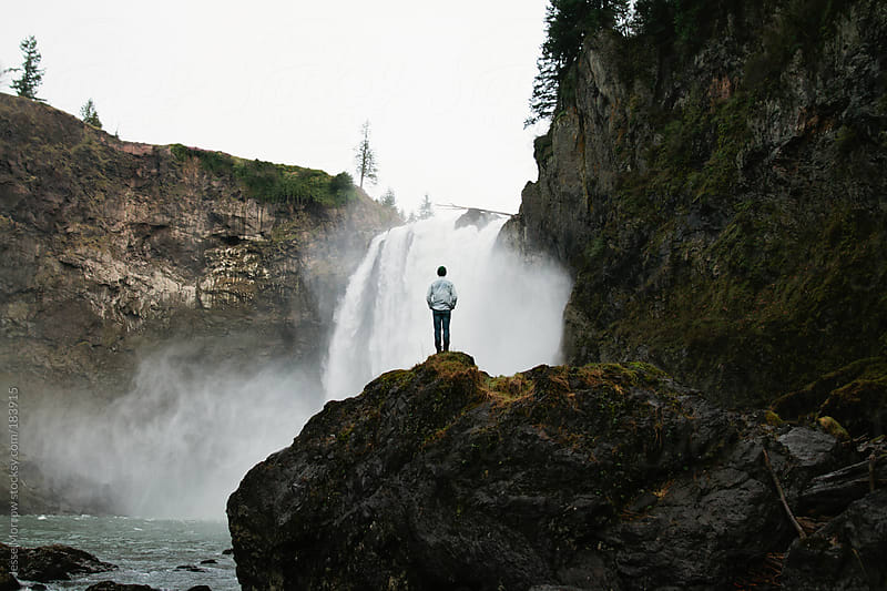 young man climbs up to waterfall by Jesse Morrow for Stocksy United