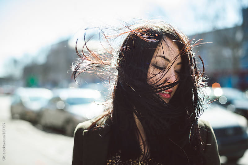 Punchy portrait of a cool young woman girl in the wind by GIC for Stocksy United