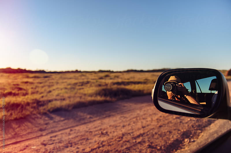 Taking photos out a car window as the sun sets on the Cape Range National Park in Western Australia by Angela Lumsden for Stocksy United