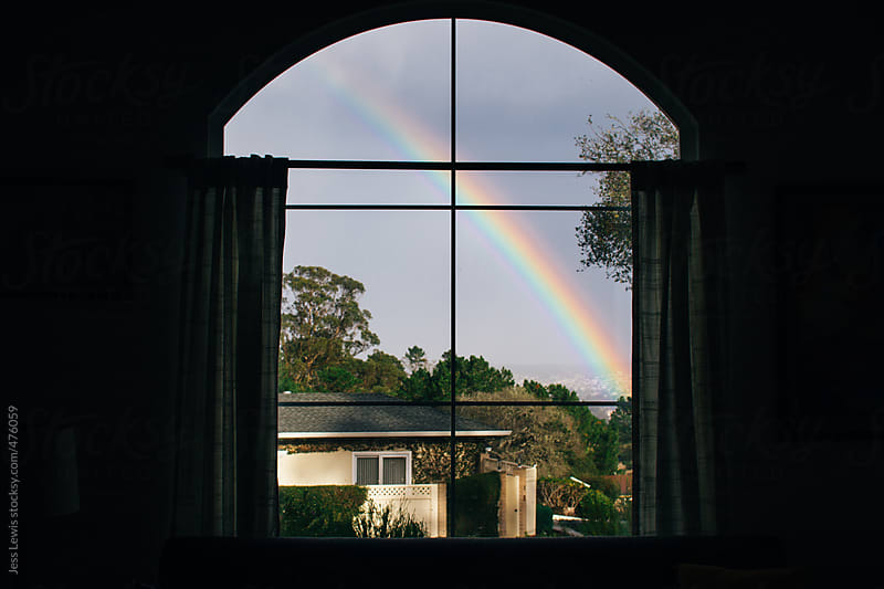 rainbow viewed through an interior window by Jess Lewis for Stocksy United