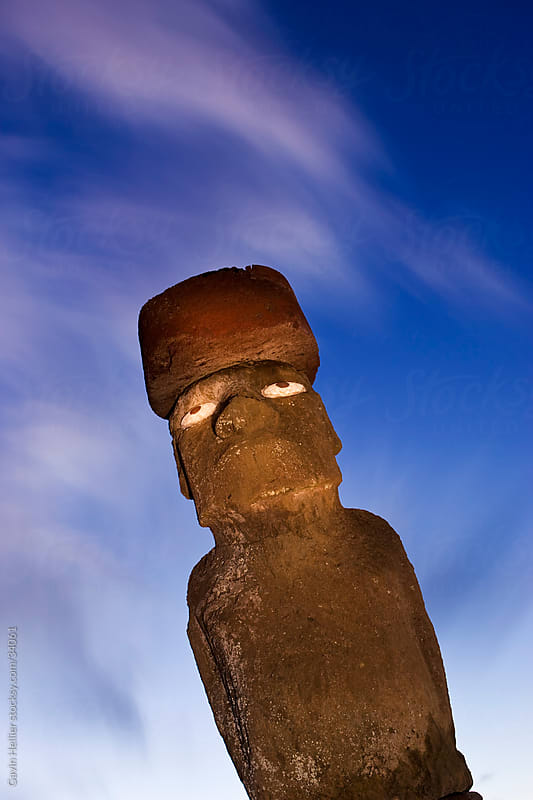 South America, Chile, Rapa Nui, Isla de Pascua (Easter Island), Moai statue Ahu Ko Te riku, the only topknotted and eyeballed Moai on the Island, illuminated at dusk by Gavin Hellier for Stocksy United