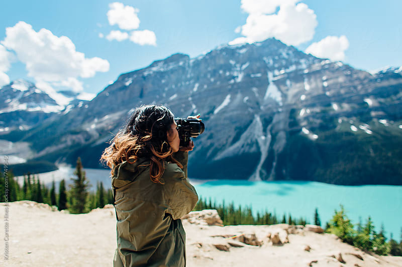 A woman ontop taking photographs of mountains by Kristen Curette Hines for Stocksy United