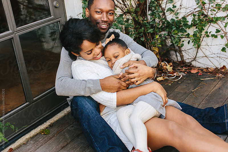 A beautiful family of three bundled up & hugging by Kristen Curette Hines for Stocksy United