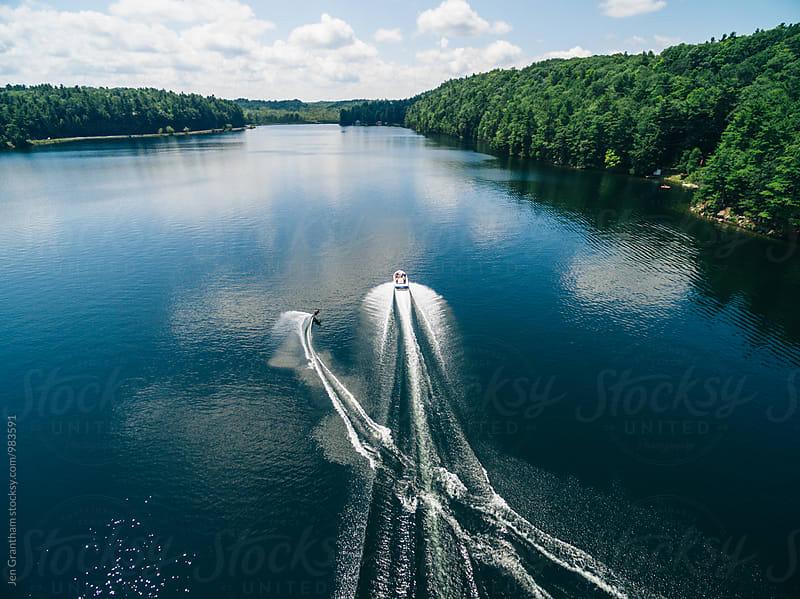 Boat pulling up a waterskiier by Jen Grantham for Stocksy United