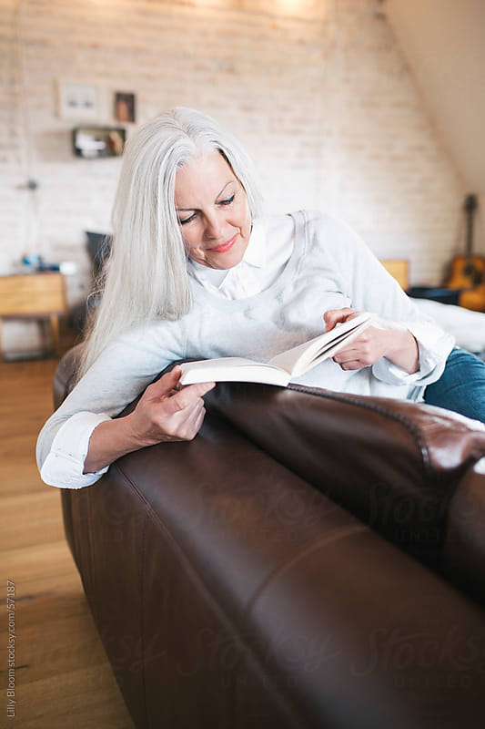 Senior woman on a sofa, reading a book by Lilly Bloom for Stocksy United