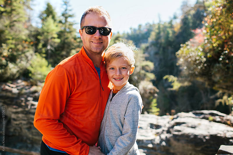 father and son on a hike in the mountains in autumn by Kelly Knox for Stocksy United