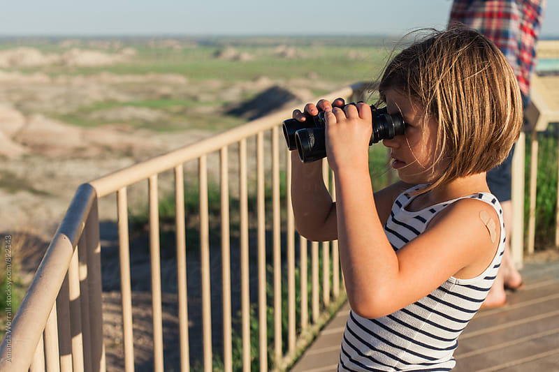 A child looking through binoculars at an observation deck in the Badlands National Park, South Dako  by Amanda Worrall for Stocksy United