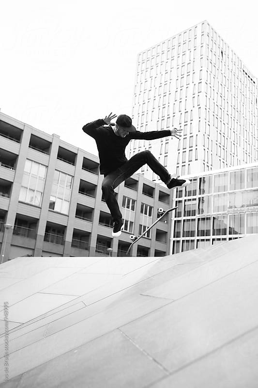 Skater doing a trick in the city by Ivo de Bruijn for Stocksy United