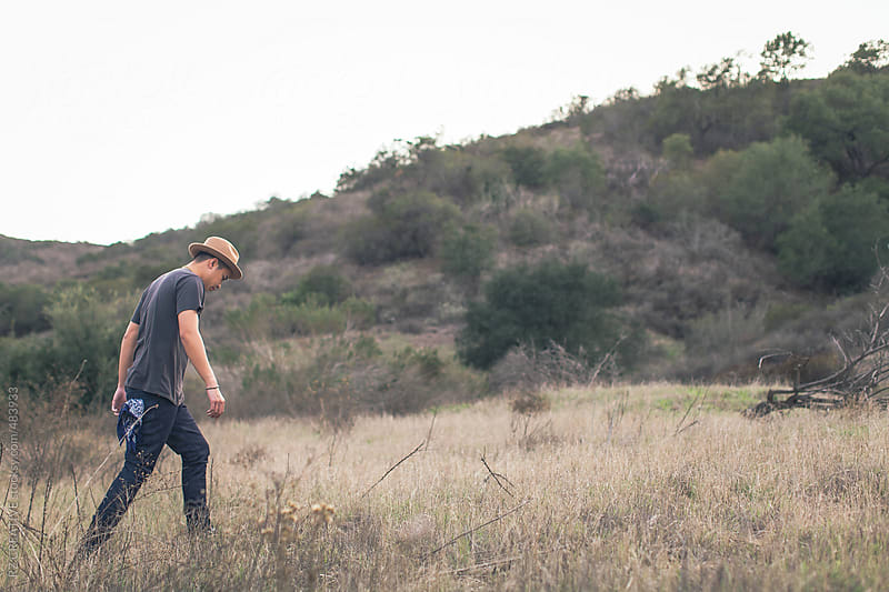 A man wearing jeans a hat walking through an open field. by RZ CREATIVE for Stocksy United