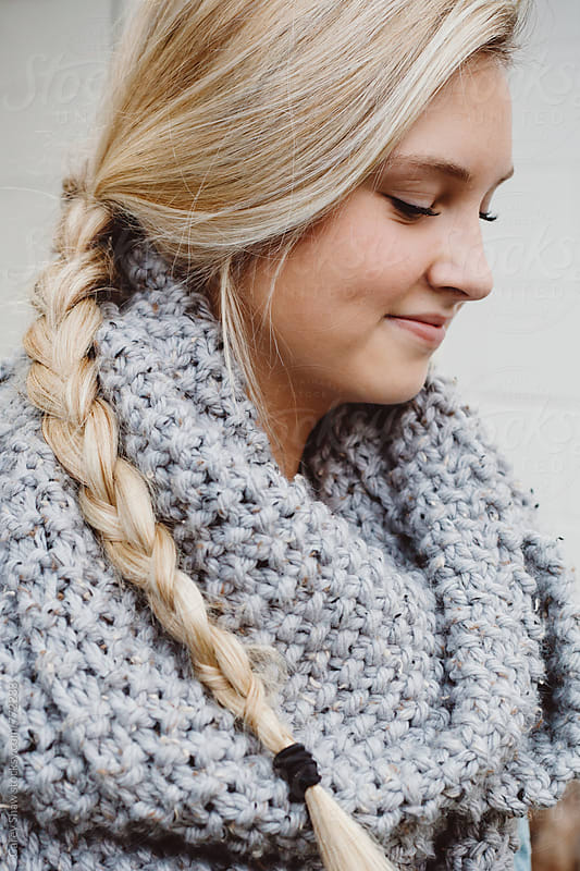 Profile of young woman wearing grey knit scarf by Carey Shaw for Stocksy United