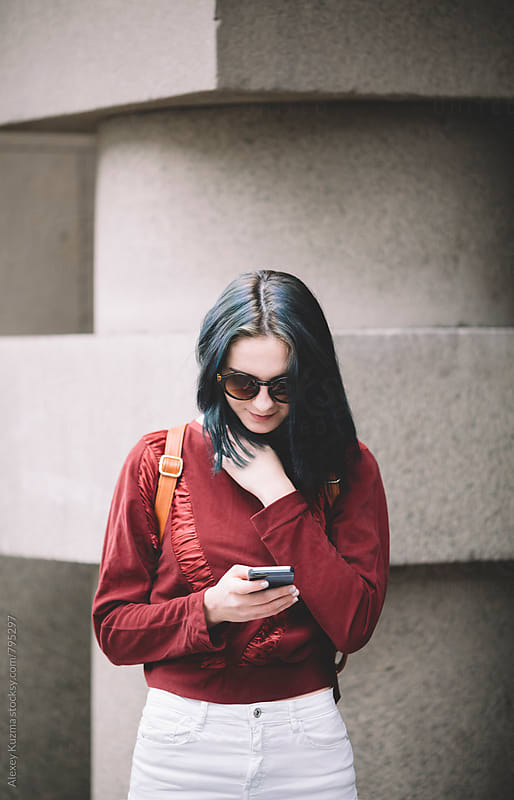 happy young woman with cell-phone by Alexey Kuzma for Stocksy United