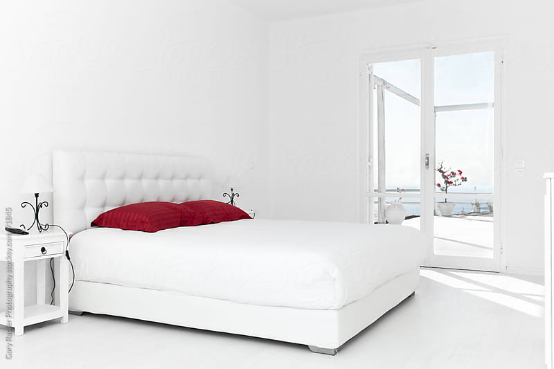 White Bedroom with Red Pillows by Gary Radler Photography for Stocksy United