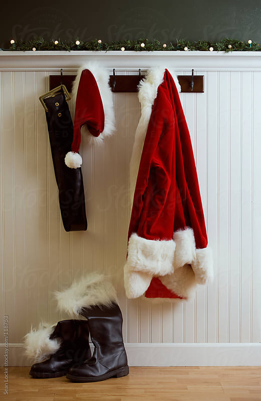 Christmas: Santa Coat and Hat Hanging With Boots On Floor by Sean Locke for Stocksy United