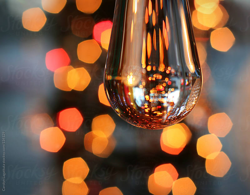 Droplet with festive lights reflected and in the background by Carolyn Lagattuta for Stocksy United