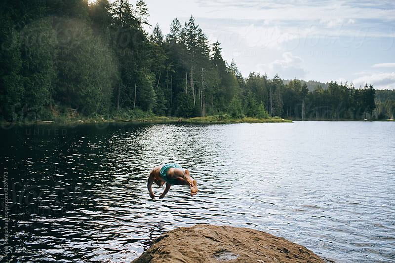 A boy jumping off into the lake by Ania Boniecka for Stocksy United