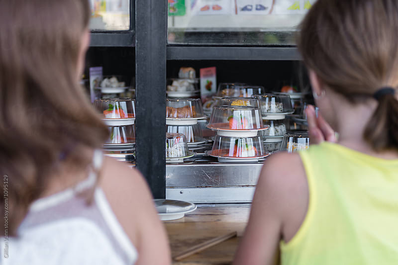 a view of the sushi train through the window, behind two young girls by Gillian Vann for Stocksy United