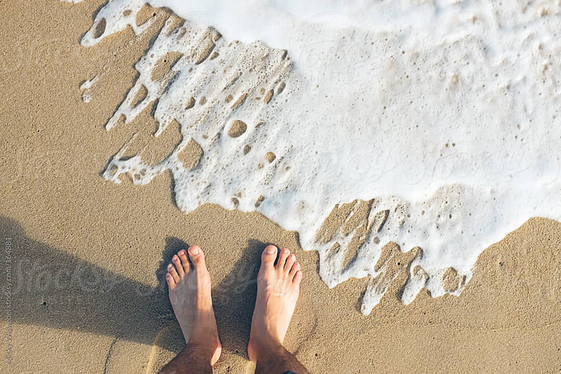 feet at the shores edge on a beach by Micky Wiswedel for Stocksy United