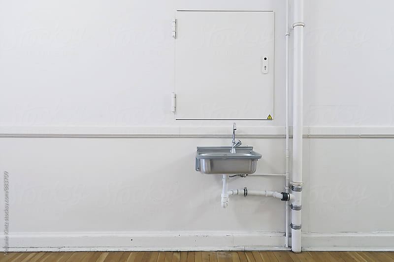 Stainless steel sink on white wall by Melanie Kintz for Stocksy United
