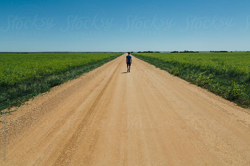 Teenage boy walking on a dirt road by Adam Nixon for Stocksy United