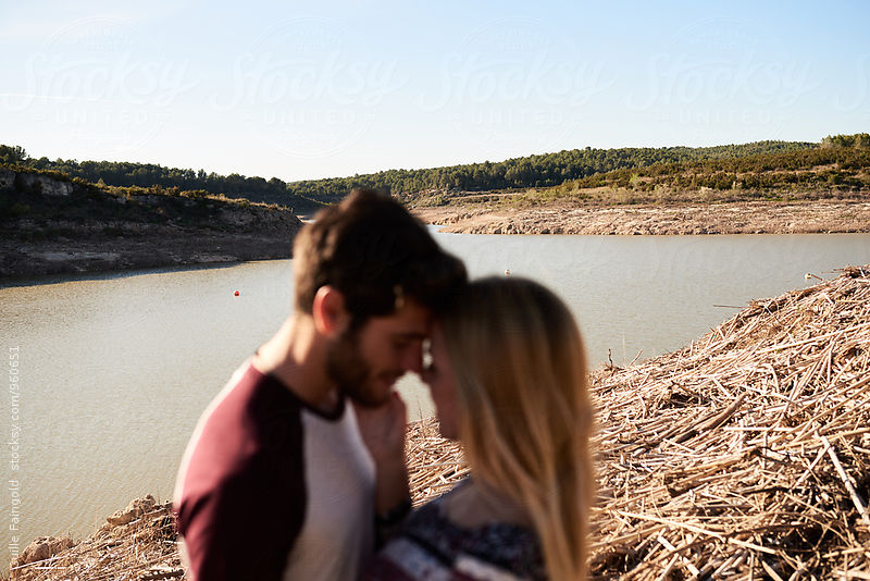 Unfocused couple against of sunny riverscape by Guille Faingold for Stocksy United