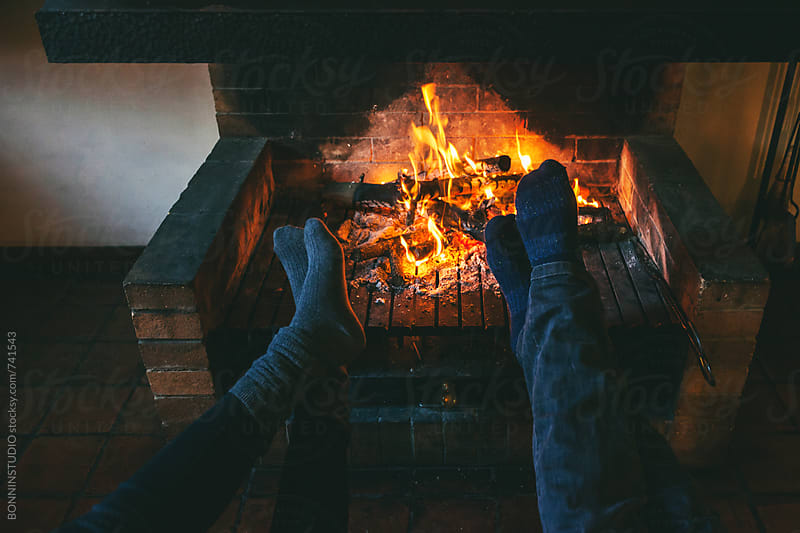 Feet of a couple warming up by the fireplace on winter. by BONNINSTUDIO for Stocksy United