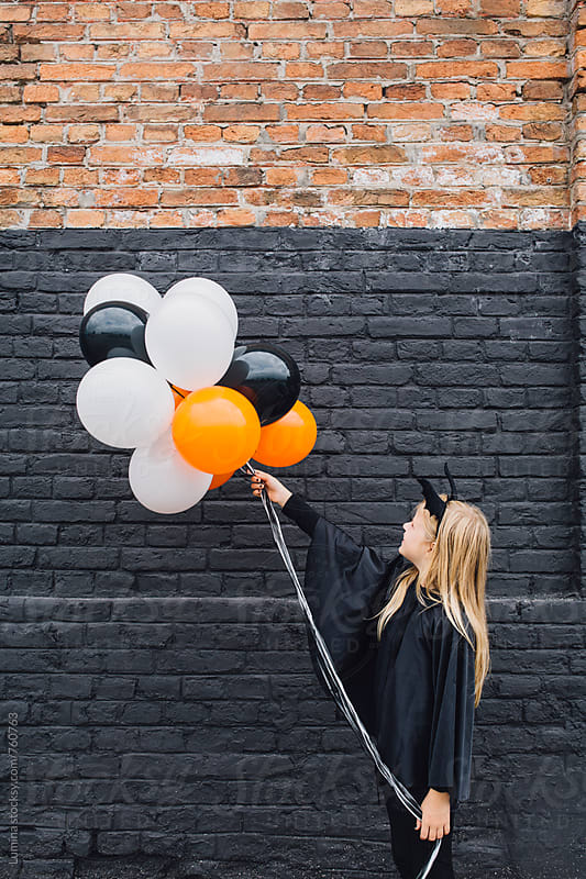 Blonde Girl in a Witch Halloween Costume Holding Balloons by Lumina for Stocksy United